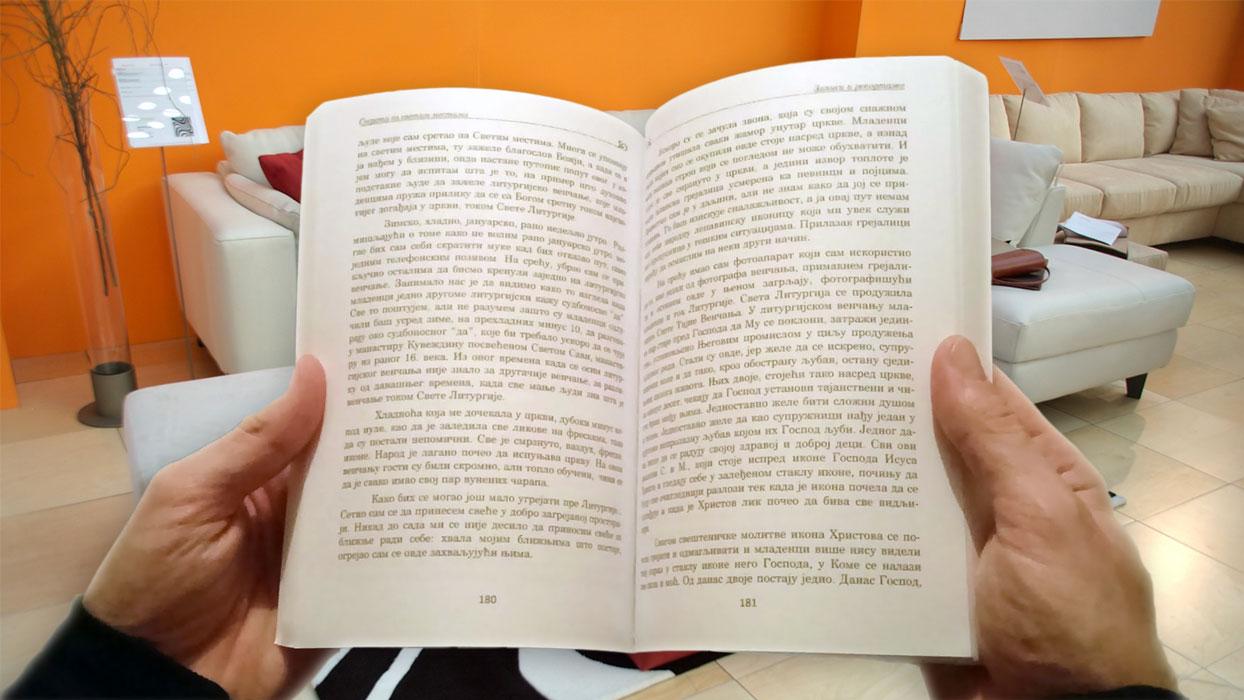 Фотографија одштампане књиге у рукама читаоца.